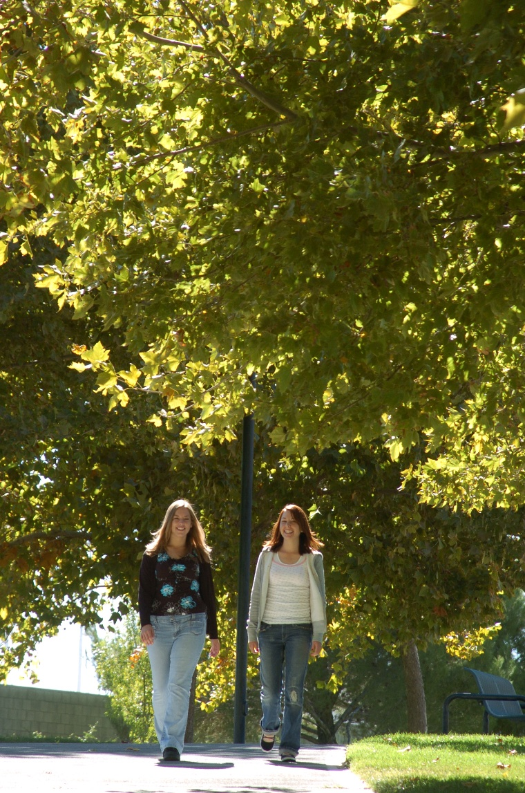 Two young women walking down a tree-lined street in Lancaster.