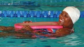 Woman in swim cap floating in pool.