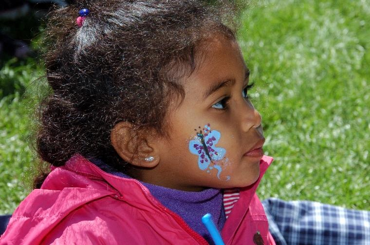 Girl getting face art at the Poppy Festival