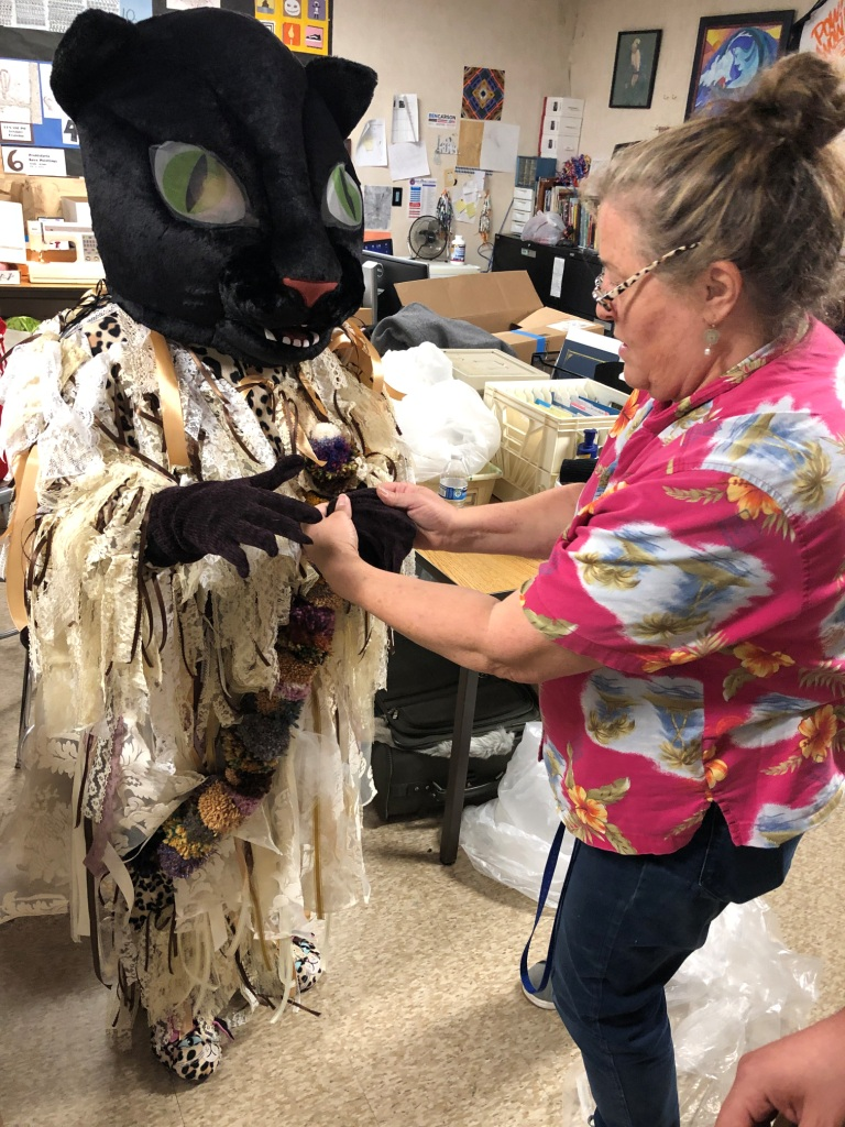 Artist Teacher Kris Holladay helping students with Nick Cave Soundsuits MOAH Lancaster CA